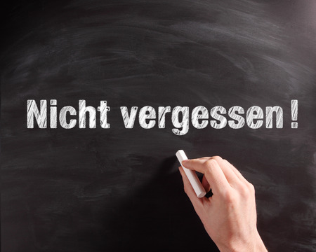 not to forget: Conceptual Handwritten Nicht Vergessen or Do not Forget Phrase on Black Chalkboard