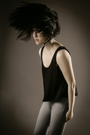 chink: Portrait of a Young Female in Casual Sleeveless Shirt and Jeans Flipping her Long Black Hair on Gray Brown Background.