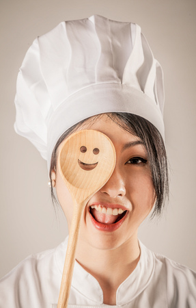 concealing: Close up Happy Young Female Chef Covering One of her Eye a Wooden Ladle with Happy Face Design. Isolated on Brown Background