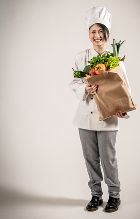 asian chef: Full Length Shot of a Happy Young Female Chef Holding a Paper Bag Full of Fresh Vegetables While Looking at the Camera. Captured in Studio on a Gray Background.