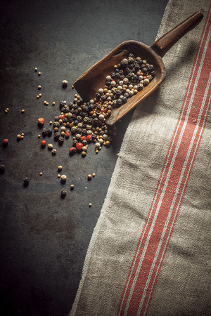 Dried mixed peppercorns, Piper nigris, spilling from a rustic vintage wooden scoop with black, red and white seeds used as a pungent flavoring and spice for food Imagens