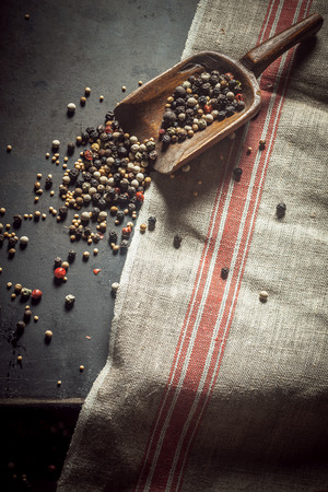 scattered: Pungent spicy dried peppercorns in assorted black, red and white spilling out of an old wooden scoop onto a kitchen counter, overhead view with copyspace on a kitchen cloth Stock Photo