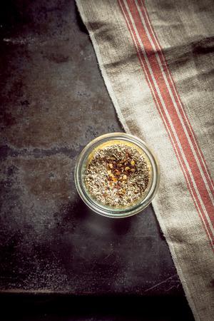 pungent: Vaso di vetro di tipo misto spezie sfregamento aromatiche e pungenti per insaporire carne e stagionatura e pesce, vista dall'alto con un panno e copyspace