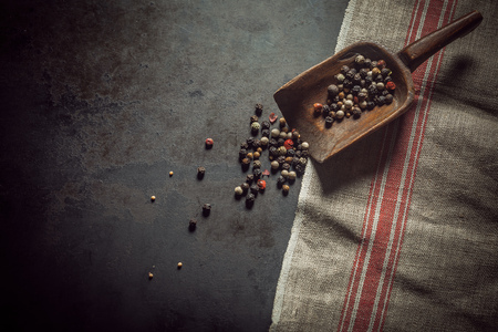 spoiling: Dried assorted peppercorns in a vintage wooden scoop spoiling out onto a rustic kitchen cloth and slate counter with copyspace, high angle view