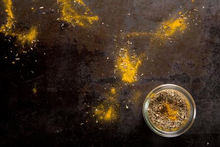 epices: Pot d'épices frotter pour faire mariner la viande et le poisson avec des restes épars de la poudre de chili sur un compteur d'ardoise, vue de dessus avec copyspace Banque d'images
