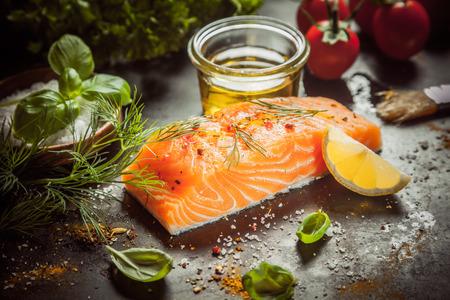 aceite de cocina: Preparar una comida gourmet de salmón con un filete de pescado suculento gruesa, aceite de oliva, hierbas, especias y condimentos frotar en un mostrador de la cocina, opinión del primer