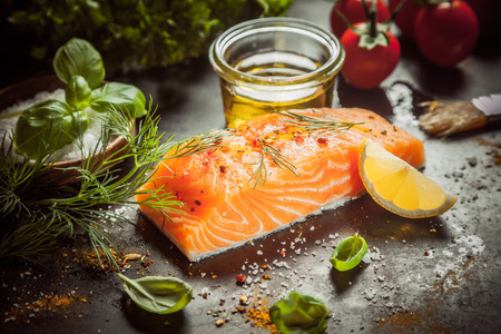 fresh salmon: Preparing a gourmet salmon meal with a thick succulent fish fillet, olive oil, herbs, spice rub and seasoning on a kitchen counter, close up view Stock Photo