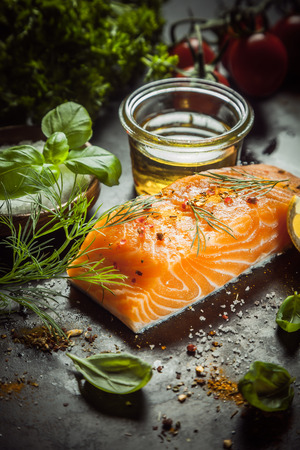 marinate: Uncooked salmon fillet with fresh basil, dill, olive oil and spices on a kitchen counter ready to cook a gourmet seafood dinner Stock Photo