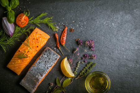 preparing food: Two portions of fresh gourmet uncooked salmon fillet displayed on a slate background with herbs, olive oil chilli peppers, tomato and onion in a savory recipe, copyspace