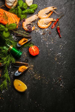 Gemengde zeevruchten voorbereid in een keuken met zalm steaks, roze garnalen en mosselen met verse kruiden en specerijen op een lei teller, bekijken van boven met copyspace Stockfoto