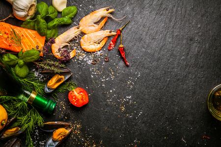 Het voorbereiden van verse vis in de keuken met gastronomische zalmfilets, roze garnalen, en gestoomde mosselen omringd door verse kruiden en specerijen, met copyspace