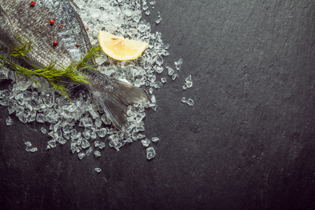 crushed by: Fresh fish on crushed ice with dill displayed with the tail visible in the top left corner of the frame on a slate background with copyspace Stock Photo