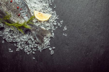 ice crushed: Verse vis op gemalen ijs met dille weergegeven met de staart zichtbaar in de linkerbovenhoek van het frame op een lei achtergrond met copyspace Stockfoto