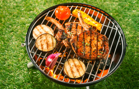 barbecue fire: Pork loin and assorted fresh healthy vegetables grilling on a barbecue outdoors on green grass in a summer lifestyle concept