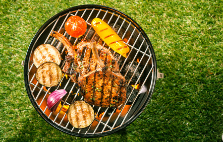 Healthy lean pork loin cutlets with assorted fresh veggies grilling over the glowing coals on a BBQ outdoors on the green lawn in a summer garden, overhead view
