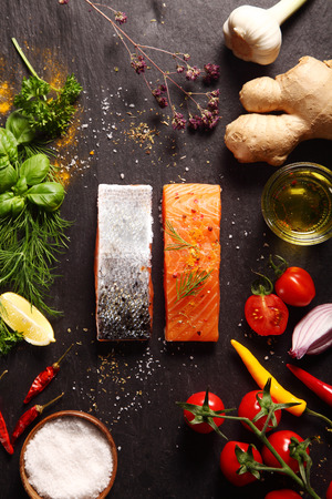 surround: Raw salmon fillets surrounded by savory ingredients including spicy root ginger, fresh herbs, tomato, chili pepper, garlic and olive oil for a gourmet dinner recipe