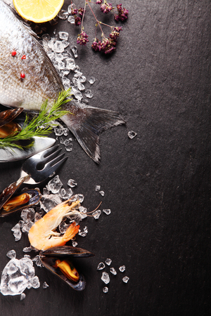 mariscos: Ingredientes frescos para una comida de mariscos con gambas de color rosa, y la cola de un pescado entero con hierbas frescas y especias en hielo picado en un contador de pizarra con copyspace
