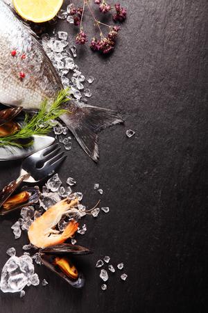 ice crushed: Verse ingrediënten voor een zeevruchten maaltijd met roze garnalen, en de staart van een hele vis met verse kruiden en specerijen op gemalen ijs op een lei teller met copyspace Stockfoto