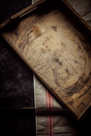 country kitchen: Empty old vintage rustic wooden kitchen tray for food preparation lying on a cloth on a kitchen counter, overhead view with vignetting Stock Photo