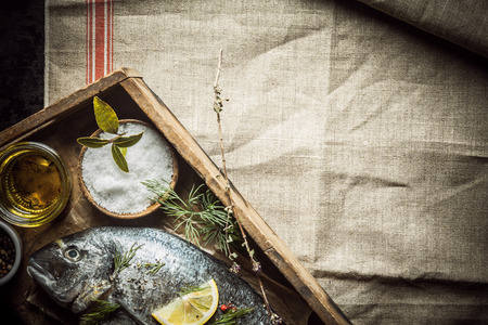gilt head: Fresh whole fish and rubbing spice and assorted fresh herbs lying on an old wooden tray ready to be marinated before cooking for dinner, overhead view on a creased cloth with copyspace Stock Photo