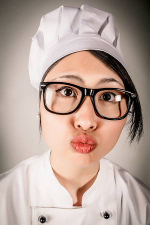 puckering lips: Fun portrait of a young female Asian chef wearing glasses and a toque making a kissing gesture puckering up her lips and leaning towards the camera Stock Photo