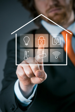 eficiencia energética: Hombre de negocios usando un elegante panel de control de la casa de activar la configuración de seguridad en un interfaz virtual transparente Foto de archivo