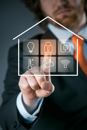 Zakenman met behulp van een slimme huis bedieningspaneel van de beveiligingsinstelling activeren op een transparante virtuele-interface