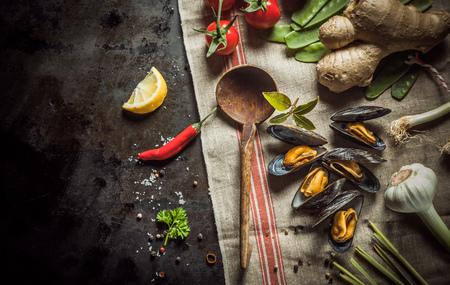 mariscos: Reci�n cocinado mejillones con ingredientes salados para preparar un aperitivo de mariscos gourmet incluyendo el ajo, aj�, ra�z de jengibre, tomate, cilantro, laurel y especias con una cuchara de madera r�stica