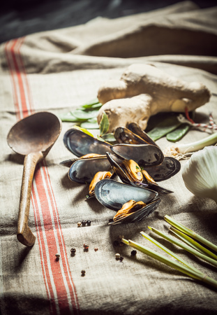 country kitchen: Boiled marine mussels with fresh ingredients for a seafood dinner being prepared in a country kitchen with a rustic wooden spoon