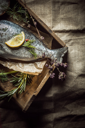 Fresh uncooked whole fish with rosemary and dill lying on crumpled brown paper on an old wooden tray, overhead view with heavy vignetting photo