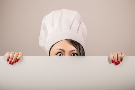 toque: Young woman chef wearing a white toque holding a blank white sign in her hands and peeking over the top with just her eyes showing and a surprised shocked expression