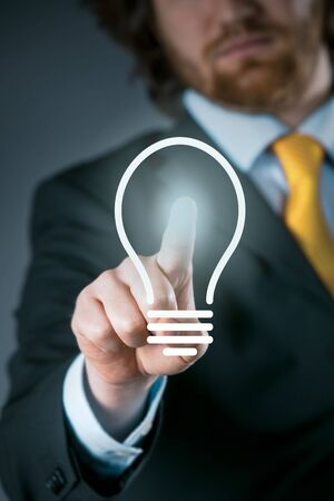activating: Man activating a light bulb icon on a virtual interface conceptual of a bright idea, inspiration, imagination or innovation in business