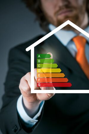 activating: Businessman activating an energy efficiency chart on a virtual interface conceptual of an efficient eco friendly energy and temperature setting on a modern smart house Stock Photo