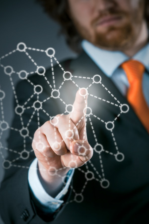 virtual community: Businessman using a network on a virtual interface activating a group or community of networked contacts in a communication concept Stock Photo