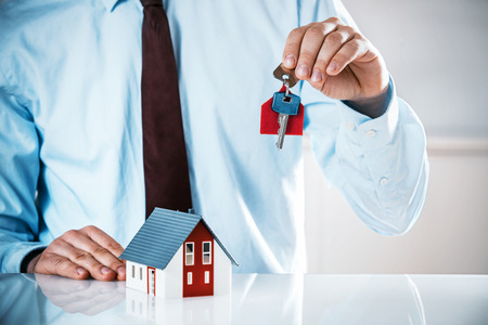 Close up Realty Male Agent at the Table Holding a House Key Up with Miniature Model House.