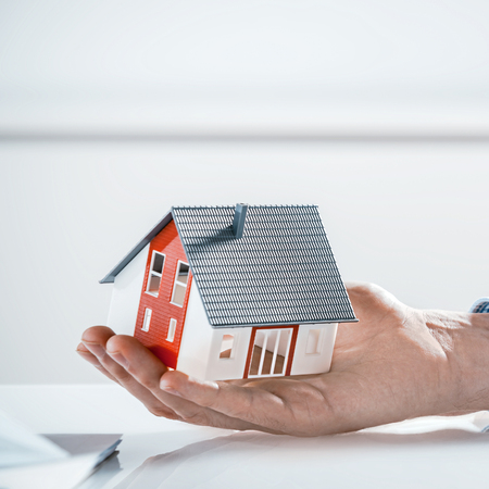 Close up Bare Hand Holding a Miniature Architectural Model House on Top of the Table with White Background.