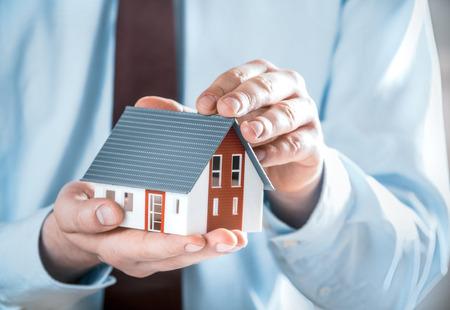 equidad: Cierre de negocios en traje de negocios con una miniatura Casa Modelo lindo Usando sus dos manos. Foto de archivo