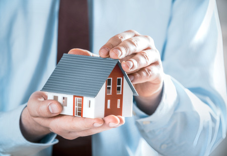 home protection: Close up Businessman in Business Suit Holding a Cute Miniature House Model Using his Both Hands.