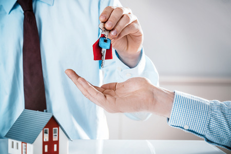 Conceptual Male Realty Agent Giving House Key to a Buyer on Top of the Table with Miniature Model House, Captured in Close up. Stock Photo