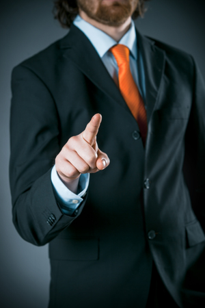 identifying: Conceptual Businessman Wearing Black Business Suit Pointing at Camera on a Gray Gradient Background, Captured in Close up. Stock Photo