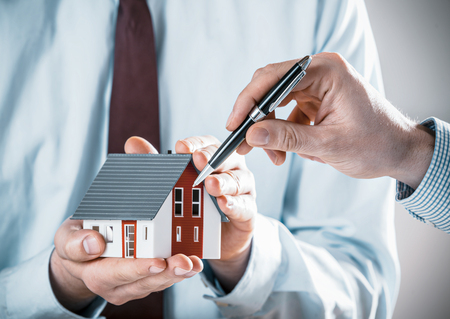 principal: Client discussing a house design with an architect pointing to the model of the house with his pen, close up of their hands Stock Photo