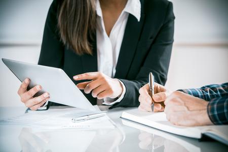 Twee mensen uit het bedrijfsleven in een vergadering bespreken van informatie op een tablet-pc en het maken van aantekeningen als ze samenwerken als een team, close-up bekijken van hun handen zittend aan een bureau