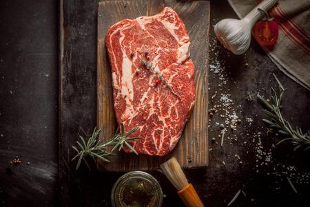 허브와 향신료 소박한 테이블에 원시 쇠고기 고기와 나무도 마 보드를 닫습니다
