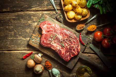 carne cruda: Cierre de carne de cerdo fresca con hierbas, especias y verduras sobre una tabla de madera r�stica, capturado en elevada.