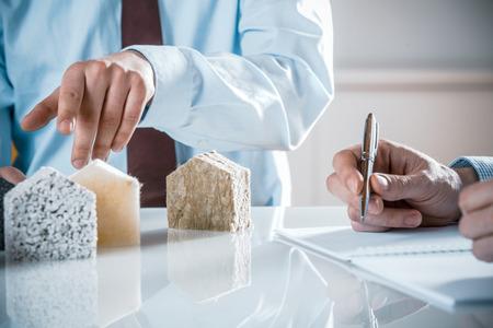 Hausbesitzer und Architekten diskutieren eine Auswahl von Dämmstoffen zeigt auf einen als Architekt erstellt den Vertrag