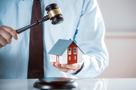 Subastador derribando una venta de la propiedad que sostiene una casa modelo como él levanta su mazo o un abogado o juez de mediar en una disputa de propiedad en los tribunales