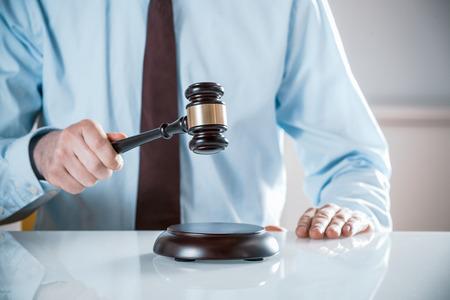 bid: Abogado, juez o subastador levantando su martillo de madera para emitir un juicio o derribar una venta al mejor postor, de cerca de las manos Foto de archivo