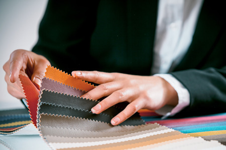Close up view of the hand of a woman checking fabric color swatches for interior decorating on a counter top