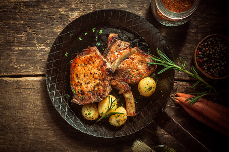 seasoned: Gourmet meal of marinated pork cutlets served with boiled baby jacket potatoes seasoned with fresh herbs in an old frying pan on a rustic wooden kitchen table