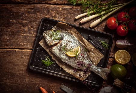 to fish: Carne de pescado en una bandeja de Negro con hierbas y especias sobre una tabla de madera rústica con verduras orgánicas. Capturado en Vista elevada.